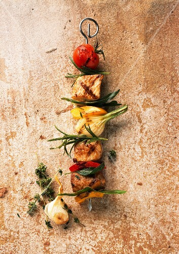A meat kebab with vegetables and herbs