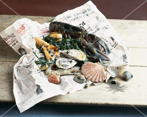 Various types of fresh seafood on a piece of newspaper