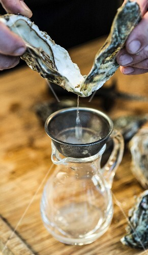 Oyster water being sieved into a jug