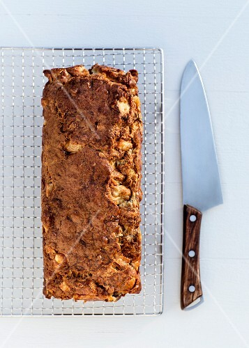 A savoury pear and walnut cake on a wire rack