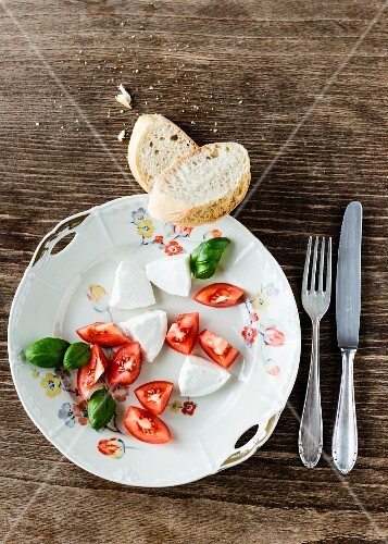 Mozzarella, tomato pieces, basil and baguette on a old floral-patterned porcelain plate