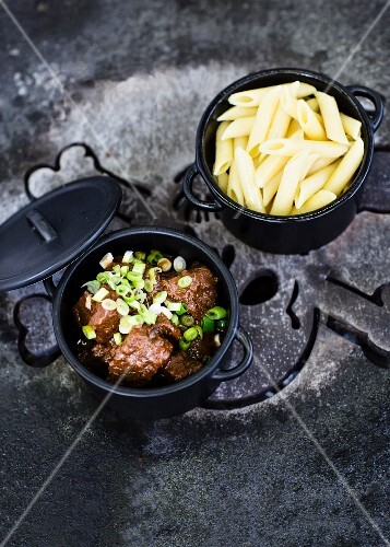 Goulash with spring onions and penne pasta in black pots
