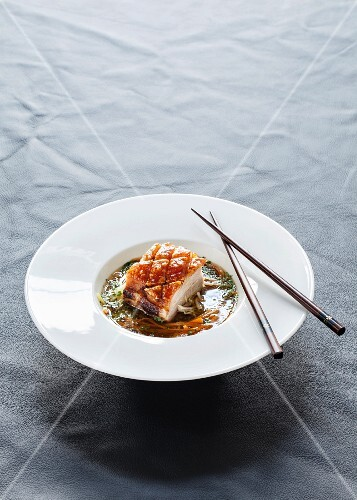 Pork belly in a lemongrass and coriander broth with vegetable strips and herbs