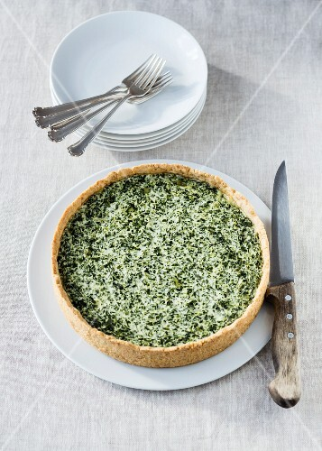 Spinach quiche on a plate with a knife
