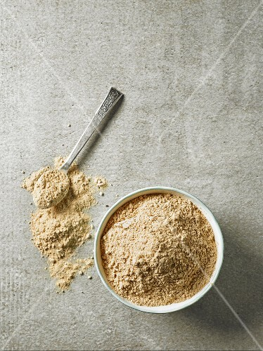 Maca powder in a bowl and on a silver spoon (seen from above)