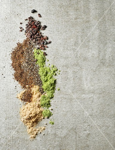 Maca powder, barley sprouts powder, chia seeds, ground flax seeds and cacao nibs on a grwy table