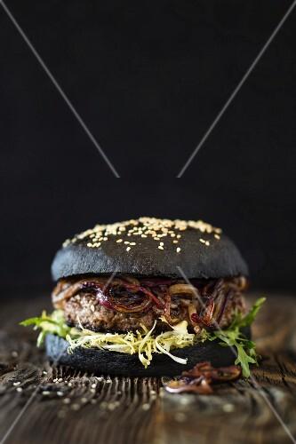 Dry Aged Hamburger mit gebratenen, roten Zwiebeln und schwarzem Burgerbrötchen