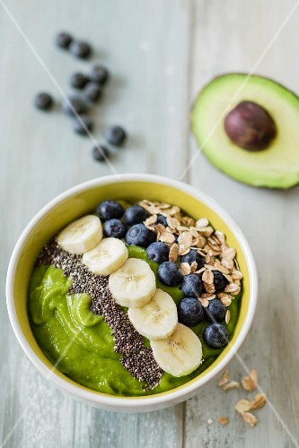 A bowl of smoothie with avocado, banana and blueberries