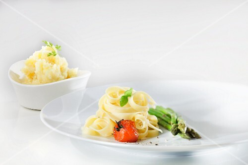Tagliatelle with sautéed cherry tomatoes, basil and green asparagus with a bowl of mashed parsley potatoes in the background