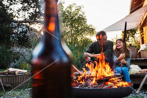 A father and daughter in a garden with a fire burning in a fire bowl