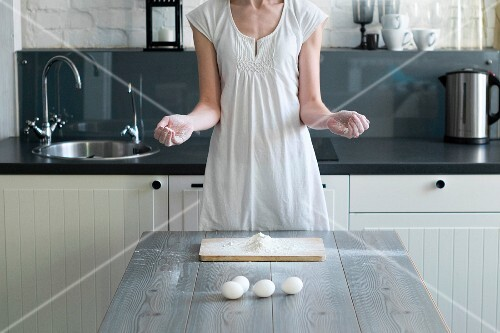 A woman with flour on her hands standing at a kitchen table