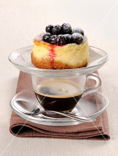 A mini blueberry cheesecake on top of a cup of coffee
