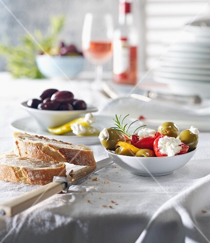Various types of antipasti with bread and olives on a laid table