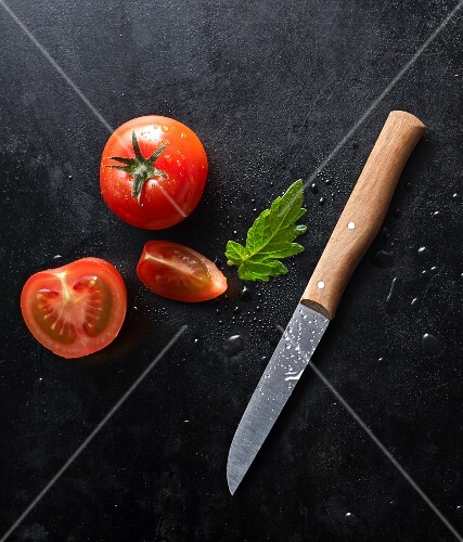 Two fresh tomatoes and a knife on a black baking tray