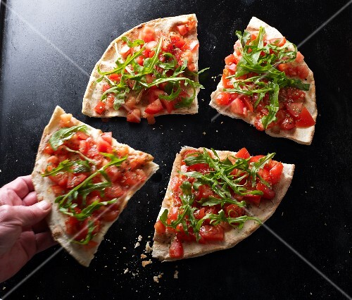 A hand taking a slice of bruschetta pizza
