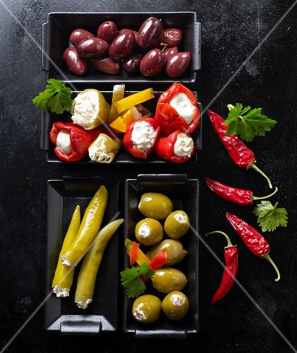 Various olives, stuffed mini peppers and jalapeños on a black baking tray