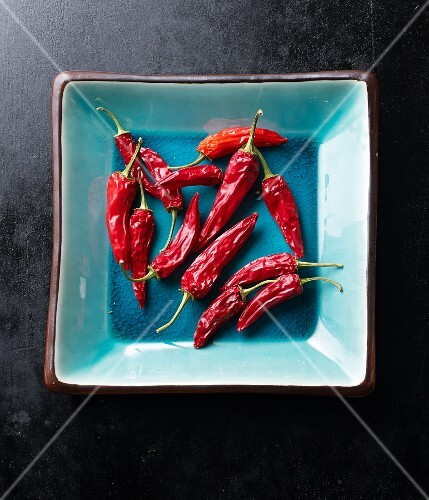 Dried red chilli peppers in a turquoise bowl