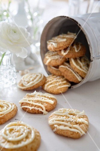 Cookies decorated with white chocolate in a storage tin
