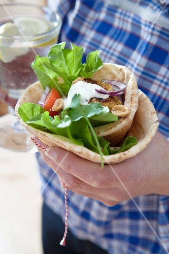 A hand holding a falafel, peanut and red onion wrap