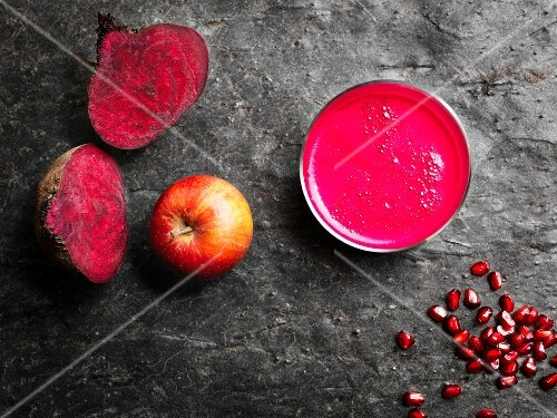 A pink superfood smoothie made with beetroot, apples and pomegranate seeds