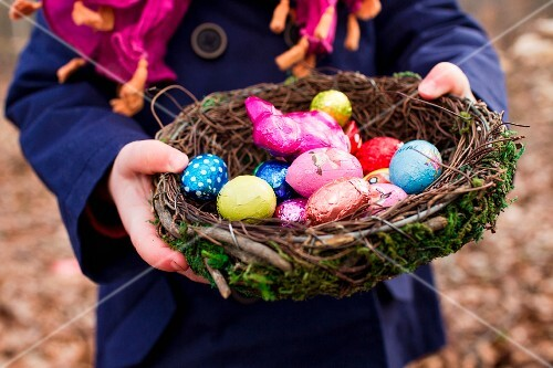 A child holding an Easter nest filled with Easter eggs