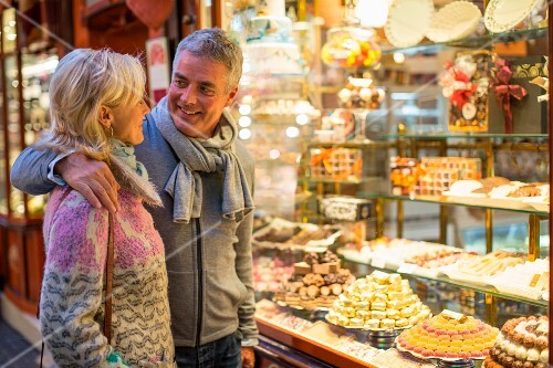 A romantic couple outside the window of a bakery (Majorca, Spain)