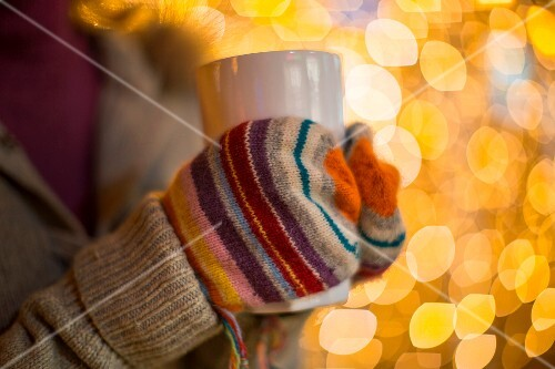 A woman wearing gloves holding a hot drink with Christmas lights in the background