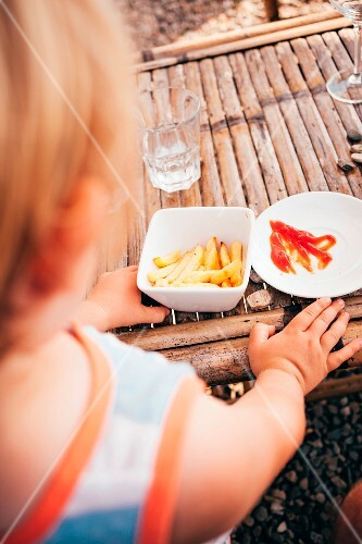 A little boy eating chips with ketchup