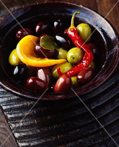 Green olives, black olives, a red chilli, an orange slice and a bay leaf in vintage bowl