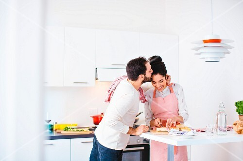 An amorous couple cooking together in the kitchen