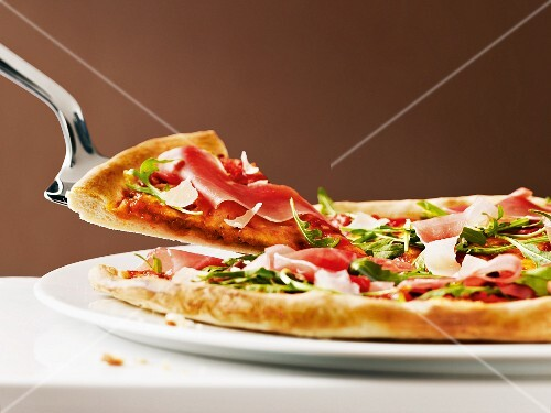 Pizza with raw ham and rocket, sliced