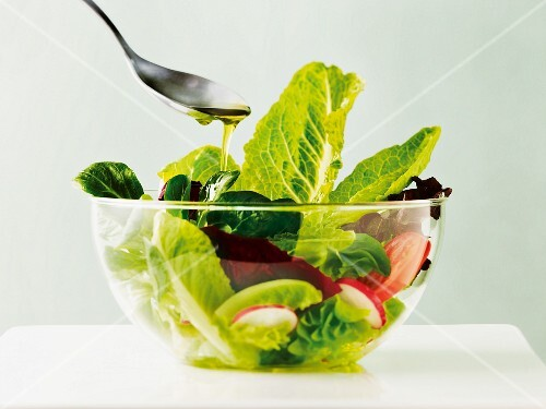 A mixed leaf salad with radishes, tomatoes and olive oil