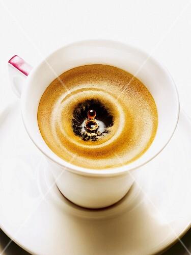 A drop falling into an espresso