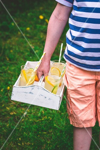 A boy carrying lemonade glasses on a tray