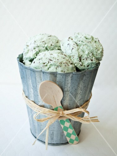 Mint chocolate chip ice cream in a tin bucket with raffia and a spoon