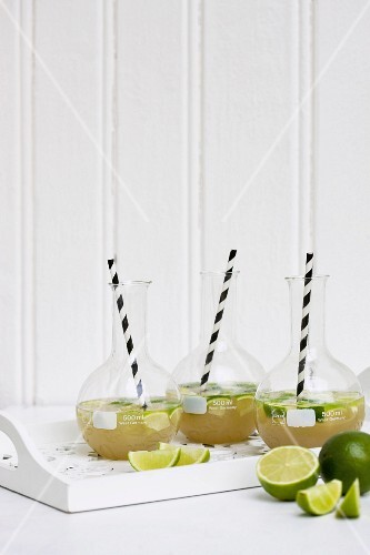 Lemonade with limes in carafes with straws