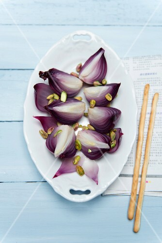 Braised red onions with pistachio nuts in a porcelain bowl on a blue wooden surface