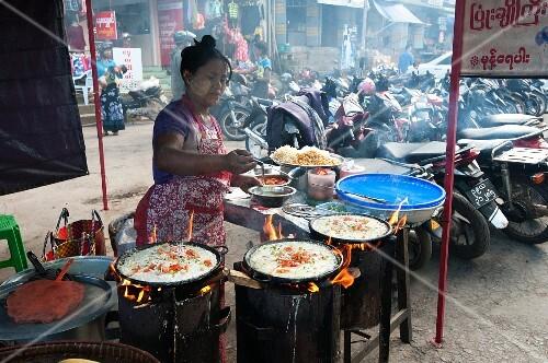 The woman preparing rice pancakes in a street kitchen (Myanmar, Burma)