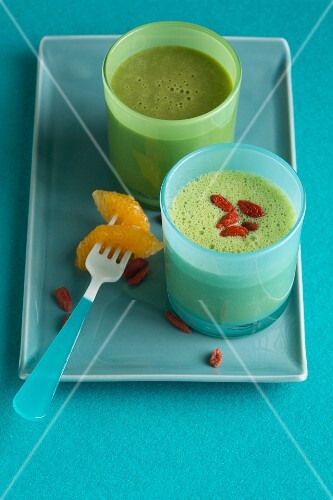 A green smoothie made with mandarin, and a banana and pineapple smoothie with goji berries