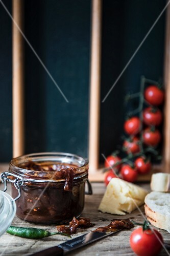 A jar of chutney with bread, cheese, cherry tomatoes and a chilli pepper