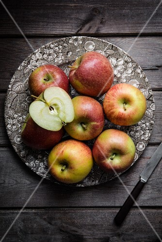 Fresh apples on a plate, one cut in half (seen from above)