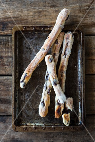 Olive breadsticks on an old baking tray