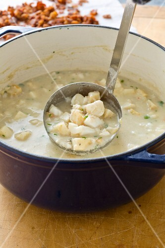 New England fish chowder in a soup pan with a ladle (USA)