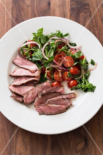 Flash fried steak with a watercress and tomato salad (seen from above)