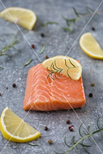 Raw salmon fillet with lemons, rosemary and pepper