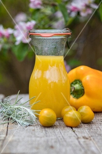 Chilled yellow pepper and tomato drink on a table outside