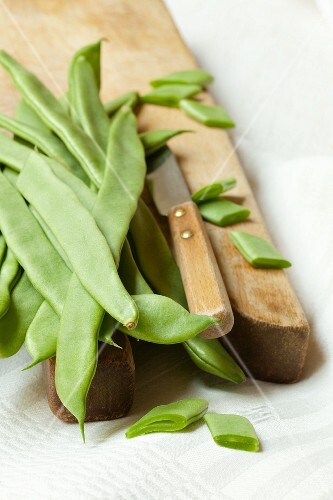 Green beans with a knife on a wooden chopping board