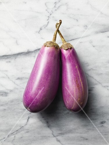 Two aubergines on a marble surface