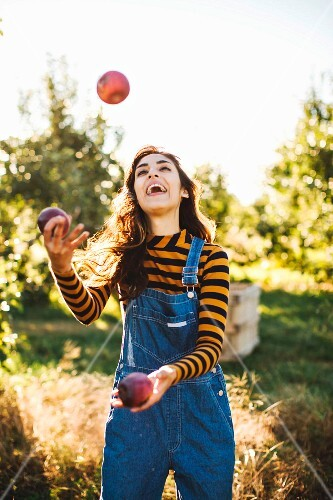 A young woman wearing dungarees juggling with apples