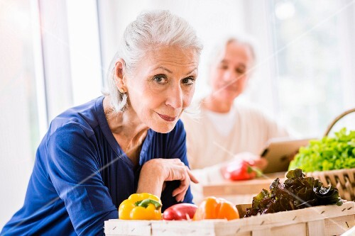 A portrait of an older lady with a crate of vegetables at a kitchen table